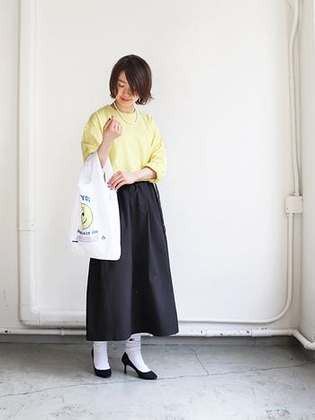 黒のロングスカートにイエローのトップスを合わせた、華やかさと上品さを両立できる着こなしです。白ソックスや黒のヒールパンプス、パールのネックレスなどを合わせれば、デイリーウェアもラグジュアリーにアップデート♪