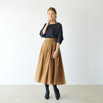 ベージュのフレアロングスカートに、黒のトップスをインしたスタイルです。女性らしい印象が強いフレアスカートに、あえて黒トップスを合わせることで、フェミニンになり過ぎないハンサムな着こなしに。アクセサリーや小物使いで、カジュアルさやガーリーさをプラスするのもおすすめです。