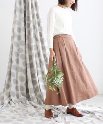 ブラウンカラーのAラインスカートに、白のトップスを合わせたナチュラルガーリーなコーデです。落ち着いた印象になりやすいブラウンカラーは、白のシンプルなトップスと合わせて柔らかく女の子らしいスタイリングに。