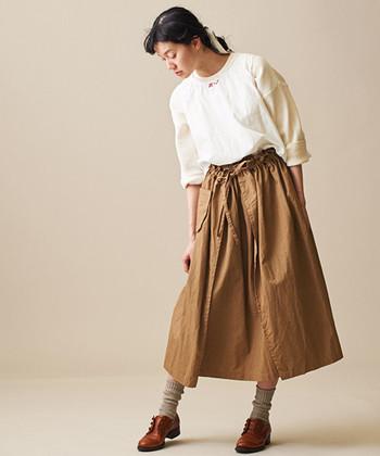 巻きエプロンをイメージして作られたというこちらのロングスカートは、くるりと巻き込んだようなデザインがアクセントに。白のスエットトップスと合わせて、プレーンな着こなしに仕上げています。ベージュの靴下と茶色のシューズなど、スカートと合わせた足元コーデがおしゃれ。