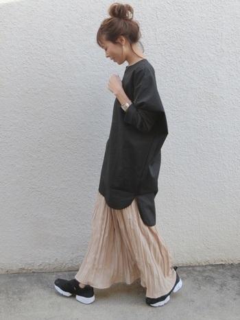 ピンクベージュのロングスカートに、黒のロング丈トップスを合わせた着こなしです。上下ゆるゆるの組み合わせで、カジュアルなのに、どこか女性らしさを感じさせるスタイリングです。足元はスニーカーでラフスタイルにしていますが、パンプスを合わせてレディにまとめても素敵です。