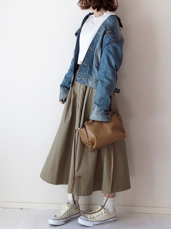 カーキのフレアロングスカートに、白トップスとデニムジャケットを合わせたスタイリングです。デニム×カーキがメンズライクな印象になりやすいので、ヘアスタイルやゆるっと羽織ったライトアウターの抜け感で、女性らしさをしっかりプラスするのがポイント♪