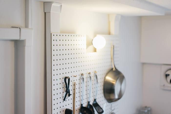 ディアウォールの木材に有孔ボードを取り付けて壁面収納に。棚よりもスリムなつくりで、場所を取りません。壁面収納は見せる収納になるのでバランスを考えながら、キッチンツールや小物を配置していきましょう。
