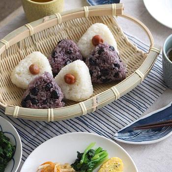 """両側に持ち手のついた""""手つき楕円ざる""""は、富山県の職人さんが丁寧に編み込んだもの。少しスリムな印象で、食卓であまり場所を取らないので、器としての用途も広がります。おにぎりとお味噌汁のシンプルな献立も、ざるに盛り付けるだで雰囲気がアップ♪"""