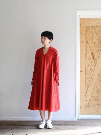 シンプルな形の赤のワンピースは、さらりと一枚で着こなすのがおすすめです。白のスニーカーと合わせてカジュアルにまとめたリラックスコーデです。