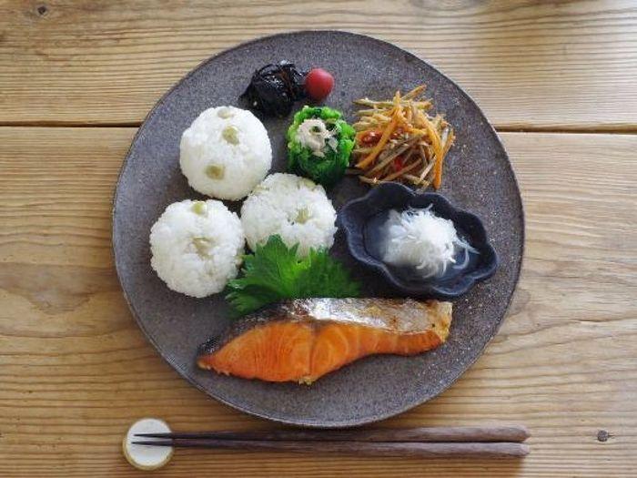ぜひ、食材の彩度が出しにくい和食にも、「黒い器」を取り入れてみてください。こちらのプレートのように、黒の小皿を重ねてのせて、丸いおにぎりを添えて…と、上でご紹介したテクニックと組み合わせれば、食卓をモダンに演出するプレートごはんの出来上がり♪ ごはんとメインのおかずに対して、副菜をちょっとずつ小盛りに…というバランスの取り方も上品ですね。