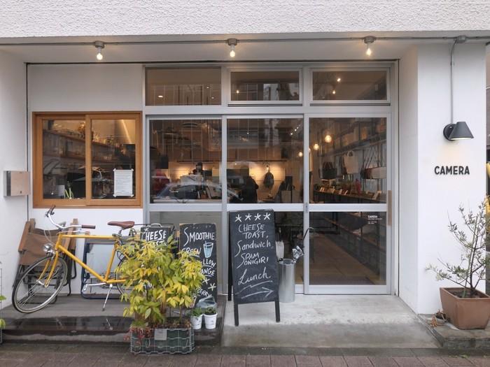 蔵前駅から国際通り沿いに位置するカフェ「CAMERA(カメラ)」。白を基調としたシンプルなデザインにガラス扉がお洒落な外観です。