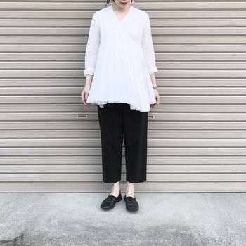 胸元から広がるプリーツラインが美しい純白のトップスは、ブラックのパンツ合わせることで引き締まった印象を叶えます。ふんわりとした素材感を残すよう合わせるパンツも、ゆったり目の物をチョイスするのがポイントです。