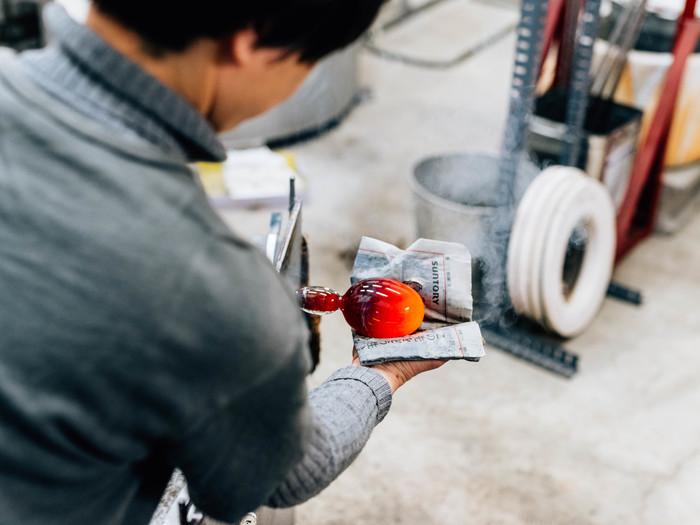 赤黒く熱をもったガラスが、黒川さんの手のなかでみるみるうちに形を変えていきます