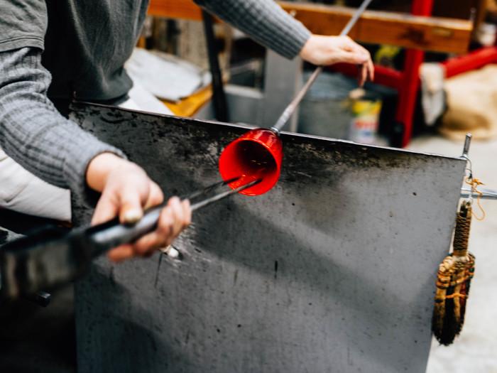 息を吹き込んだガラスの先端をカットし、吹き竿を回しながらそこにジャックとよばれる道具を入れ、コップの形を形成していきます。「この作業がなかなか難しくて苦手なんです」と黒川さん
