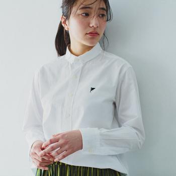 """スタンダードなボタンダウンシャツは、日本製の仕立ての良さも魅力的です。胸元のワンポイント刺繍は、ネ・ネットの新しいブランドアイコン『フラッグマーク』。今後、ベーシックなアイテムにはこのマークがつくとのこと。ブランドロゴで主張するのではなく、""""分かる人だけ分かる""""さり気なさが心地よい。"""