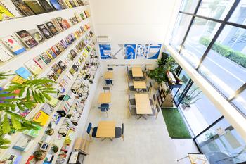 明るい光が差し込む店内は、天井高5mなので、解放感溢れる空間。センスの良いテーブルや椅子が用意され、壁一面が本棚に。本は、自由に読むことができ、購入も可能だそうです。