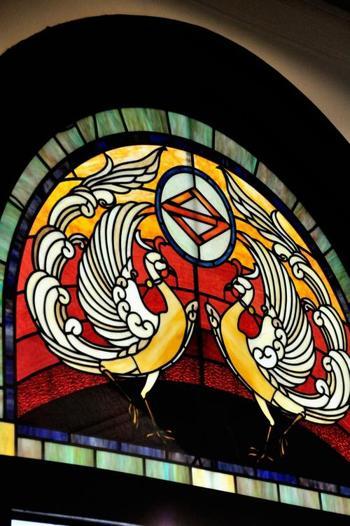 館内2階にあるステンドグラスの色彩は色褪せることなく、訪れる人の心を打つ美しさです。絵柄の円の中にあるは「ハマ」の文字を菱形にデザインした横浜市の「き章」です。