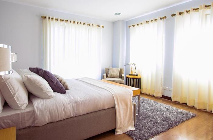 ベッドの枕元が窓に向かないよう窓辺を避けて設置されている配置例です。大きな掃き出し窓がありますが、適度な距離をとられています。カーテンは足元からの冷気を防げるよう長めに設置し、夜はしっかり締めましょう。 このように床にラグを敷くのも冷気を防ぐために良い方法です。