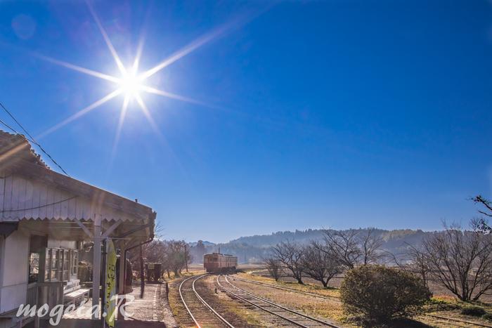 太陽が眩しく輝き、青い空とレトロな駅舎と電車が絵になりますね。