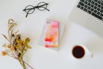 「森と、朝焼け」と言うデザインのスマホケース。暖かみのある色彩が女性らしくで素敵です。