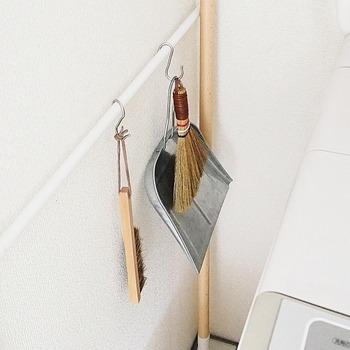 洗濯機の横につっぱり棒をかけて、お掃除道具を賢く収納。S字フックにかごを掛ければ、洗濯バサミなどの小物類も収納できます。