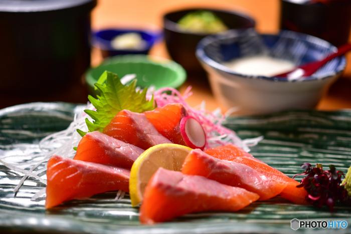例えば、上の写真のお刺身の場合、メインカラーはお刺身の赤(オレンジ)。その周りにツマの白、ワサビや大葉などの葉物の緑、レモンの黄色、最後に海藻の黒で全体を引き締めています。 お刺身のメインカラーをより引き立たせるように、サブカラーを考えながら盛り付けるのがポイントです!
