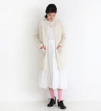 リネンニットで作られたロングカーディガンは、ミルク色の様な柔らかなカラーが素敵なアイテム。白のワンピースと合わせたワントーンコーデに、ピンクの靴下がほどよい差し色になっています。