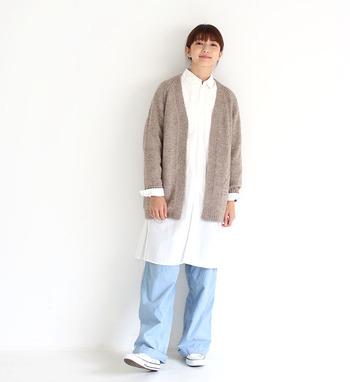 白のロングシャツに、薄色のデニムパンツを合わせたシンプルなコーディネート。濃い色のベージュのカーディガンはさっと羽織れて、少し肌寒い春の日にもぴったりです。ナチュラルカラーを組み合わせているので、レイヤードが重たくならないのもポイント。