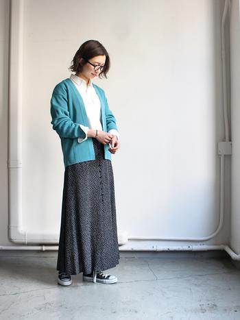 緑がかったキレイなブルーのカーディガンに、黒のロングスカートを合わせた着こなしです。インナーには白シャツを合わせて、爽やかなブルーのカーディガンを主役にしたスタイリングに。