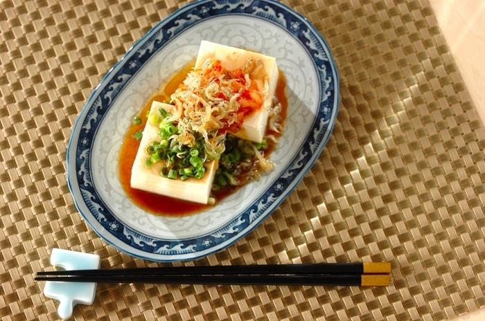 カリカリにのジャコがたっぷりのった韓国風冷奴。ゴマ油の風味がアクセントになって、箸が進む美味しさです。青ネギ、キムチ、豆腐の白の組み合わせが美しく、さらに濃い色合いの器を選ぶことで、上品な雰囲気に…。