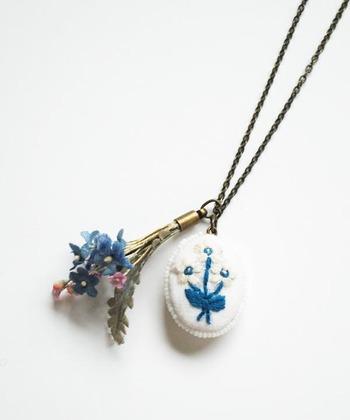 コサージュブランド「la fleur(ラ・フルール)」が手がけたミニブーケと、刺繍アーティストKanae Entaniさんによる花模様の刺繍パーツが寄り添っているネックレス。素朴な温もりのある作品です。