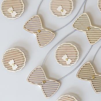 ゴムが付いたリボンの蝶ネクタイと、ブローチのセット。ヒノキの素材で作った繊細なストライプが特徴。ふんわりとほのかに漂うヒノキの良い香りがポイント。