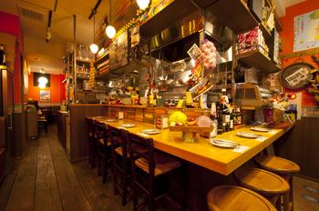 オープンキッチンを囲むカウンターも、大勢で料理を囲めるテーブル席もあります。鮮やかなオレンジ色の壁にスペインタイルなどもあしらわれた、明るく陽気な店内です。
