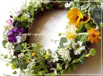 手間がかかる生の花もドライフラワーもちょっと・・・という方には、アーティフィシャルフラワーがおすすめ。アーティフィシャルフラワーは人工的に作られた花材のため、メンテナンスは時々埃をとる程度でOK。造花を集めたリースなので場所を選ばず飾ることができます。  こちらの作品はスイートピーやパンジーに、ナチュラルなグリーンを合わせたリース。様々な形のグリーンや大きさの異なる花をリズミカルにレイアウトしています。
