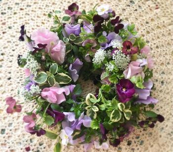 春らしいスイートピーやビオラが彩るテーブルリース。ピンク~紫の配色トーンに補色のグリーンがあいまって、全体感を美しく際立たせます。