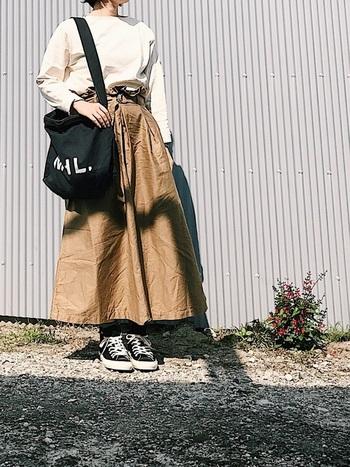 シンプルな白のカットソーをロング丈のスカートにインして。スニーカーやバッグを黒にすれば、ぼんやりとした印象になりません。