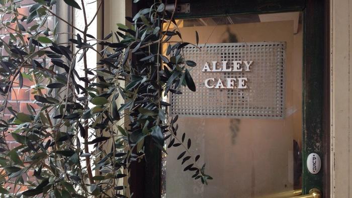 """「アリーカフェ」は、公園口を出て2~3分歩いたビルの3階にあります。店名の""""alley""""には、""""路地裏・細道・散策""""などの意味があり、さりげなく掲げてある看板は、まさに隠れ家のような雰囲気。"""