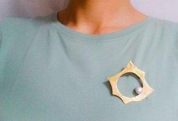 真鍮の多角形の中に一粒のパール。アーティスティックな雰囲気が漂うブローチで、Tシャツからよそゆきワンピースまで、いろいろなものに似合う力を持っています。