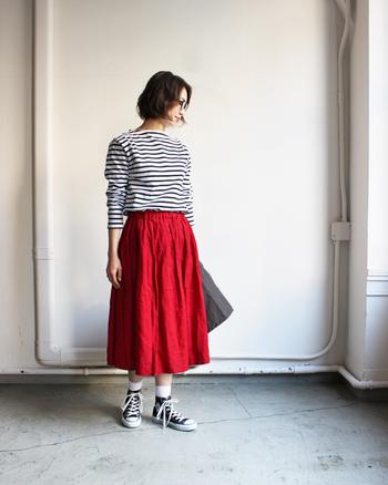 シンプルなモノトーンボーダーは、ビビッドカラーのボトムスと合わせるのも◎鮮やかな赤のギャザーフレアスカートと女性らしいボートネックシャツをチョイスして、フェミニンカジュアルな雰囲気に着こなしています。