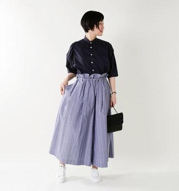 スカートのようにも見えるストライプのワイドパンツは、ギャザーの入ったウエストラインが特徴的な一枚。あえてダークトーンのシャツを合わせてボトムスにインすることで、大人の上品コーデの完成です。