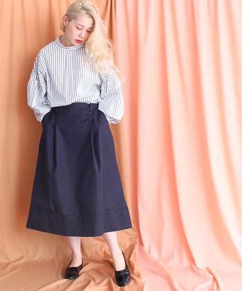 袖の部分にボリュームがあるストライプシャツは、ロングスカートのボトムスにインして細見えシルエットに。引締め色のネイビーカラーで、シンプルなのに上品なお嬢様風コーデの完成です。