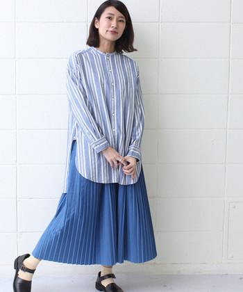 長めのストライプシャツに、同系色のプリーツスカートを合わせたスタイリング。ロングアイテム同士の組み合わせはバランスが難しいですが、トーンをまとめることで全体的にまとまりが出てスッキリした印象になりますね。