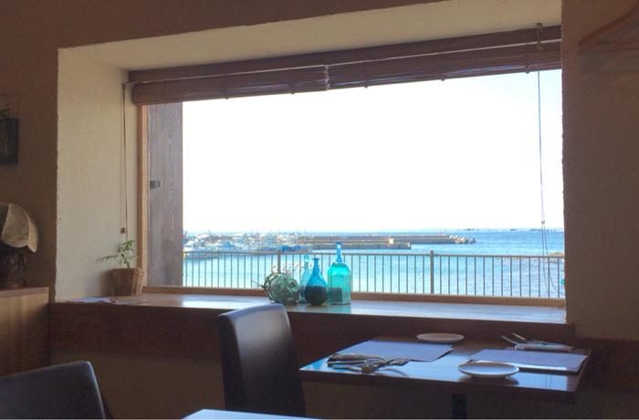 テーブル16席、カウンター6席の小さなイタリアンのお店です。窓際の席からは、こんな風に海が見えますよ。
