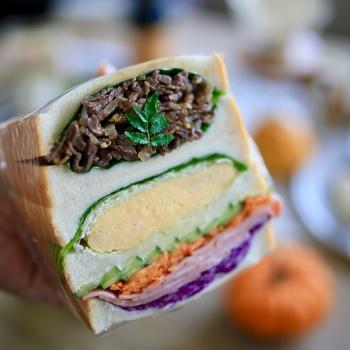 おかずを大胆にもパンに挟めば、ボリューム満点のわんぱくサンドに!しぐれ煮、厚焼き玉子、野菜…色とりどりで楽しいランチタイムが過ごせそう。
