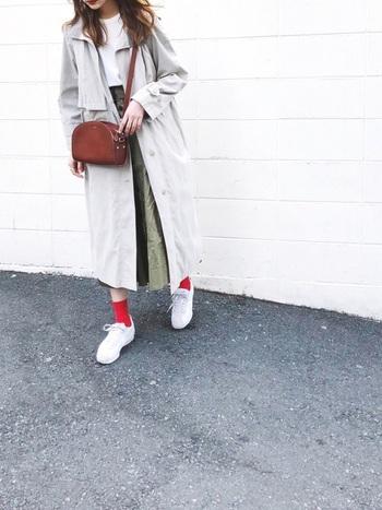 NIKEの白スニーカーに赤いソックスが差し色になっていてとってもオシャレ♪Tシャツにカーキのロングスカート+トレンチコートのきれいめスタイルでも、NIKEのスニーカーなら思いのまま街歩きできそうですね。