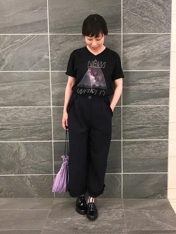 黒地のTシャツにデザインされたグラフィクを際立たせるために、パンツと靴も黒で統一。ストライプ柄の靴下もアクセント。さらに、デザインに使われているパープルと同系色の巾着バッグでさり気なくリンクさせています。