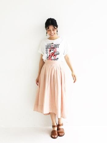 インパクトの強いプリントにピンク色がアクセントになったポップなTシャツは、淡いピンク色のフレアスカートを合わせて優しいイメージで着こなして。色を馴染ませるだけで印象が変わります。
