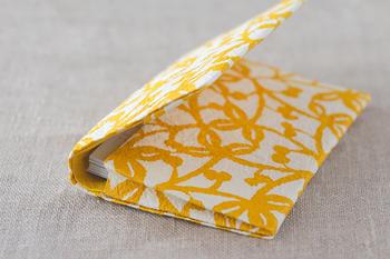 表面に柄をプリントせずに、「型染め」という、型を使って染色する手法で柄をつけているため、紙の繊維にしっかりと色が入るので、折り曲げて使う名刺入れも、折り山の色がはげることなく使用できます。