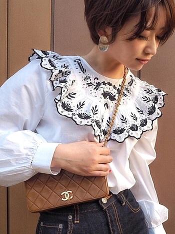 襟元にインパクトのあるZARAの刺繍ブラウスとハイブランドのポシェット使いで、お高見え必至のコーデ。デニムを合わせたひとつ大人のカジュアルスタイルを楽しんで。