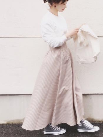 ふわっと広がるAラインのシルエットが素敵な、ベージュのストライプロングスカート。シンプルな白トップスをタックインして、上品カジュアルな着こなしに仕上げています。足元はスニーカーでカジュアルダウンしていますが、もっときちんと感を出したい日には、ヒールを合わせても良いですね♪