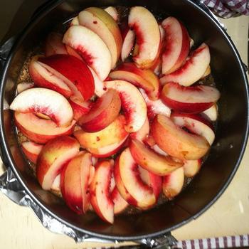アップサイドダウンケーキは、まずは砂糖で作ったキャラメルを型の底に注ぎ、その上にフルーツを隙間なく敷き詰めていきます。りんごなどは、レンジにかけて少し柔らかくすると、扱いやすいようです。型は、丸型でもスクエア型でもOK。