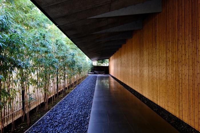 本館脇にある石畳の通路です。手入れされた竹林の木漏れ日が、竹を施した美術館の外壁に差し込み、心地良い空間を作り出しています。