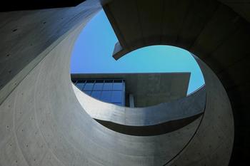 螺旋階段から上を見ると、独特なフォルムの中から美術館の外観と青々とした空が切り取られて姿をあわします。日によって、また時間によって複雑多様な表情を見せてくれるデザインです。