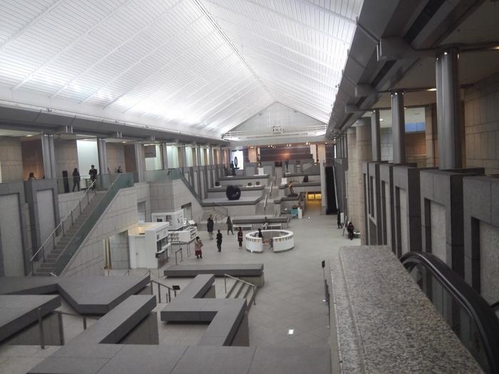 エントランスは高さ20mもの吹き抜けになっており、開放的な雰囲気です。建物には御影石がふんだんに使われています。エントランスの左右には全長100mにもなる階段状の展示空間が広がっています。